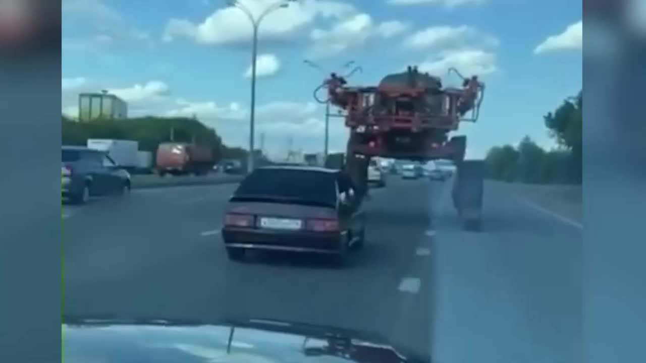 Mới- nóng - Clip: Ô tô liều lĩnh chui qua gầm máy kéo như trong phim hành động